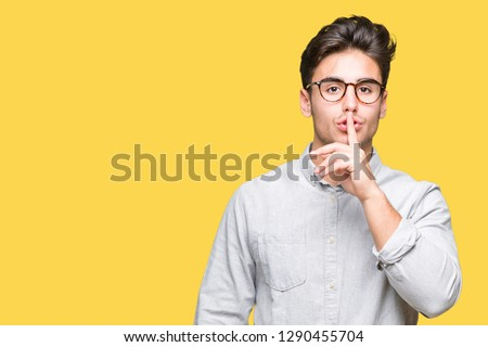 Young handsome man wearing glasses over isolated background asking to be quiet with finger on lips. Silence and secret concept.
