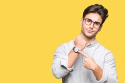 Young handsome man wearing glasses over isolated background In hurry pointing to watch time, impatience, upset and angry for deadline delay