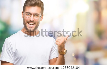 Young handsome man wearing glasses over isolated background smiling with happy face looking and pointing to the side with thumb up. #1233042184