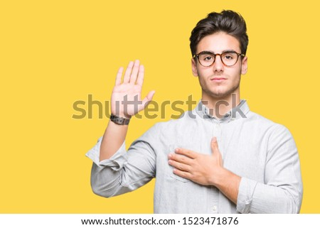 Young handsome man wearing glasses over isolated background Swearing with hand on chest and open palm, making a loyalty promise oath Foto d'archivio ©