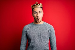 Young handsome man wearing golden crown of prince over isolated red background afraid and shocked with surprise expression, fear and excited face.