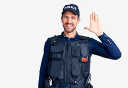 Young handsome man wearing police uniform waiving saying hello happy and smiling, friendly welcome gesture