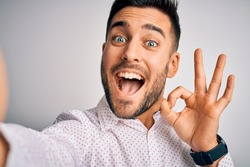 Young handsome man wearing shirt making selfie by the camera over white background doing ok sign with fingers, excellent symbol