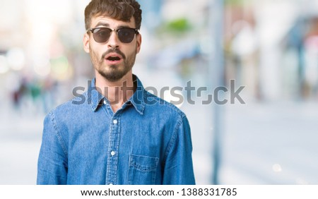 Young handsome man wearing sunglasses over isolated background afraid and shocked with surprise expression, fear and excited face. #1388331785