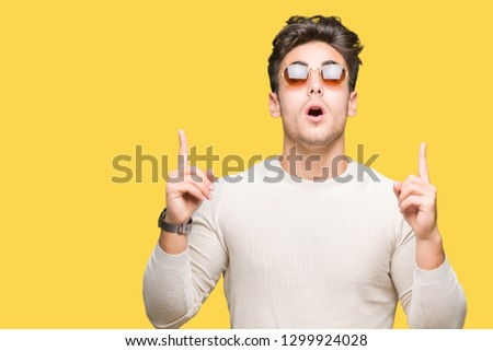 Young handsome man wearing sunglasses over isolated background amazed and surprised looking up and pointing with fingers and raised arms.