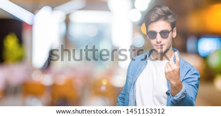 Young handsome man wearing sunglasses over isolated background Beckoning come here gesture with hand inviting happy and smiling #1451153312