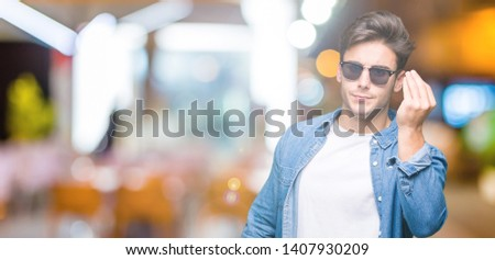 Young handsome man wearing sunglasses over isolated background Doing Italian gesture with hand and fingers confident expression #1407930209