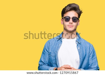 Young handsome man wearing sunglasses over isolated background Hands together and fingers crossed smiling relaxed and cheerful. Success and optimistic