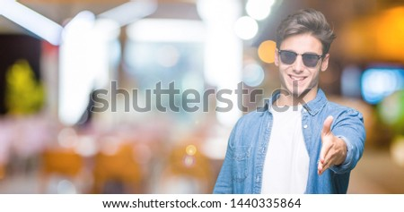 Young handsome man wearing sunglasses over isolated background smiling friendly offering handshake as greeting and welcoming. Successful business. #1440335864
