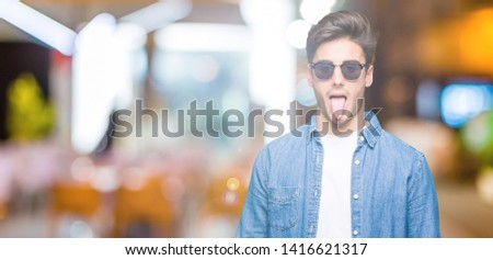 Young handsome man wearing sunglasses over isolated background sticking tongue out happy with funny expression. Emotion concept. #1416621317