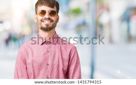 Young handsome man wearing sunglasses over isolated background with a happy and cool smile on face. Lucky person. #1431794315