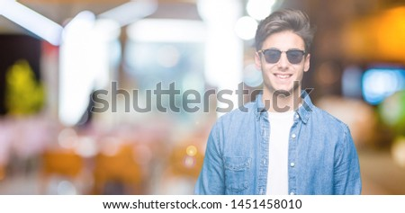 Young handsome man wearing sunglasses over isolated background with a happy and cool smile on face. Lucky person. #1451458010