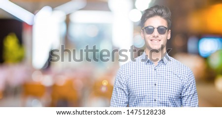 Young handsome man wearing sunglasses over isolated background with a happy and cool smile on face. Lucky person. #1475128238