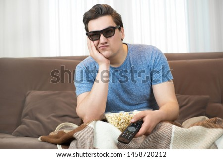 young handsome man wearing sunglasses watching movie eating popcorn clicking remote control looks disappointed #1458720212