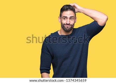 Young handsome man wearing sweater over isolated background confuse and wonder about question. Uncertain with doubt, thinking with hand on head. Pensive concept. #1374345659