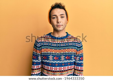Young handsome man wearing wool hat and colorful sweater with serious expression on face. simple and natural looking at the camera.  Stockfoto ©