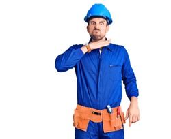 Young handsome man wearing worker uniform and hardhat in hurry pointing to watch time, impatience, looking at the camera with relaxed expression