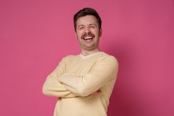 Young handsome man wearing yellow sweater standing over pink background smiling and laughing hard out loud because funny crazy joke