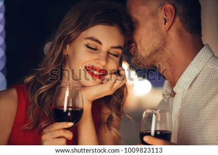 Young handsome man whisper to his gorgeous woman while have romantic dinner and drinking wine on valentines day
