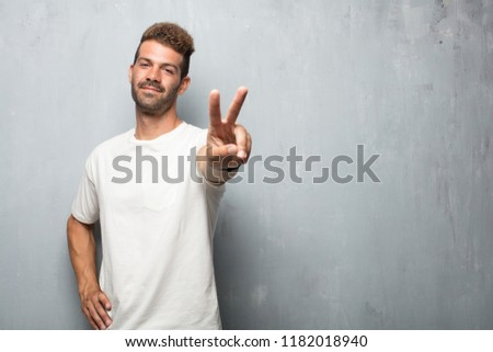 young handsome man with a proud, happy and confident expression; smiling and showing off success while gesturing victory, giving an