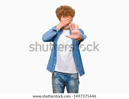 Young handsome man with afro hair wearing denim jacket covering eyes with hands and doing stop gesture with sad and fear expression. Embarrassed and negative concept.