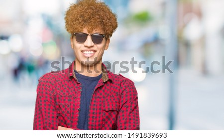 Young handsome man with afro hair wearing sunglasses happy face smiling with crossed arms looking at the camera. Positive person. #1491839693
