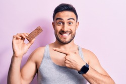 Young handsome man with beard eating energy protein bar over isolated pink background Smiling happy pointing with hand and finger