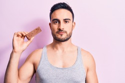 Young handsome man with beard eating energy protein bar over isolated pink background thinking attitude and sober expression looking self confident