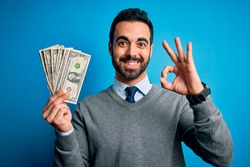 Young handsome man with beard holding bunch of dollars banknotes over blue background doing ok sign with fingers, excellent symbol