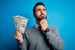 Young handsome man with beard holding bunch of dollars banknotes over blue background serious face thinking about question, very confused idea