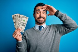 Young handsome man with beard holding bunch of dollars banknotes over blue background stressed with hand on head, shocked with shame and surprise face, angry and frustrated. Fear and upset for mistake