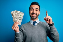 Young handsome man with beard holding bunch of dollars banknotes over blue background surprised with an idea or question pointing finger with happy face, number one