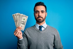 Young handsome man with beard holding bunch of dollars banknotes over blue background with a confident expression on smart face thinking serious