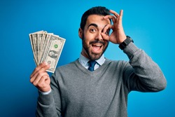 Young handsome man with beard holding bunch of dollars banknotes over blue background with happy face smiling doing ok sign with hand on eye looking through fingers