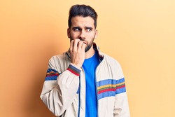 Young handsome man with beard wearing casual jacket looking stressed and nervous with hands on mouth biting nails. anxiety problem.