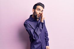 Young handsome man with beard wearing casual shirt hand on mouth telling secret rumor, whispering malicious talk conversation