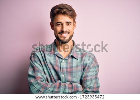 Young handsome man with beard wearing casual shirt standing over pink background happy face smiling with crossed arms looking at the camera. Positive person.
