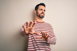 Young handsome man with beard wearing casual striped t-shirt standing over white background disgusted expression, displeased and fearful doing disgust face because aversion reaction. With hands raised