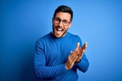Young handsome man with beard wearing casual sweater and glasses over blue background clapping and applauding happy and joyful, smiling proud hands together