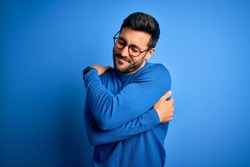 Young handsome man with beard wearing casual sweater and glasses over blue background Hugging oneself happy and positive, smiling confident. Self love and self care