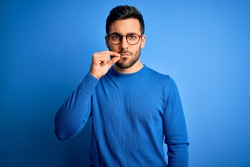 Young handsome man with beard wearing casual sweater and glasses over blue background mouth and lips shut as zip with fingers. Secret and silent, taboo talking