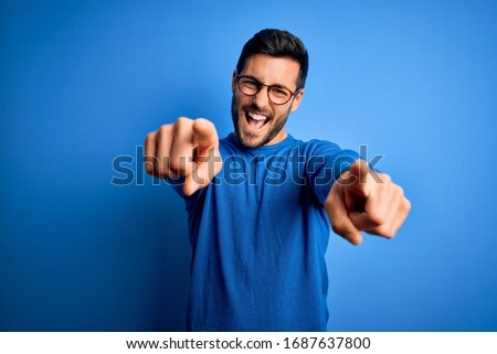 Young handsome man with beard wearing casual sweater and glasses over blue background pointing to you and the camera with fingers, smiling positive and cheerful Stock photo ©
