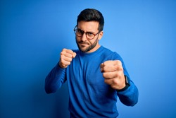 Young handsome man with beard wearing casual sweater and glasses over blue background Punching fist to fight, aggressive and angry attack, threat and violence