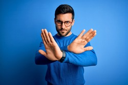 Young handsome man with beard wearing casual sweater and glasses over blue background Rejection expression crossing arms doing negative sign, angry face