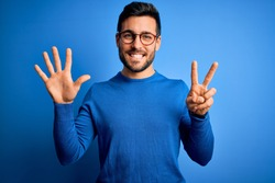 Young handsome man with beard wearing casual sweater and glasses over blue background showing and pointing up with fingers number seven while smiling confident and happy.