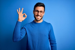 Young handsome man with beard wearing casual sweater and glasses over blue background smiling positive doing ok sign with hand and fingers. Successful expression.