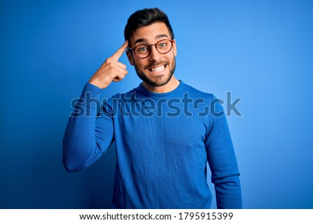 Photo of  Young handsome man with beard wearing casual sweater and glasses over blue background Smiling pointing to head with one finger, great idea or thought, good memory