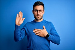 Young handsome man with beard wearing casual sweater and glasses over blue background Swearing with hand on chest and open palm, making a loyalty promise oath