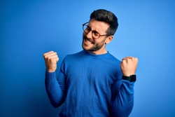 Young handsome man with beard wearing casual sweater and glasses over blue background very happy and excited doing winner gesture with arms raised, smiling and screaming for success. Celebration