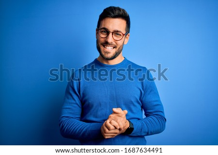 Young handsome man with beard wearing casual sweater and glasses over blue background with hands together and crossed fingers smiling relaxed and cheerful. Success and optimistic